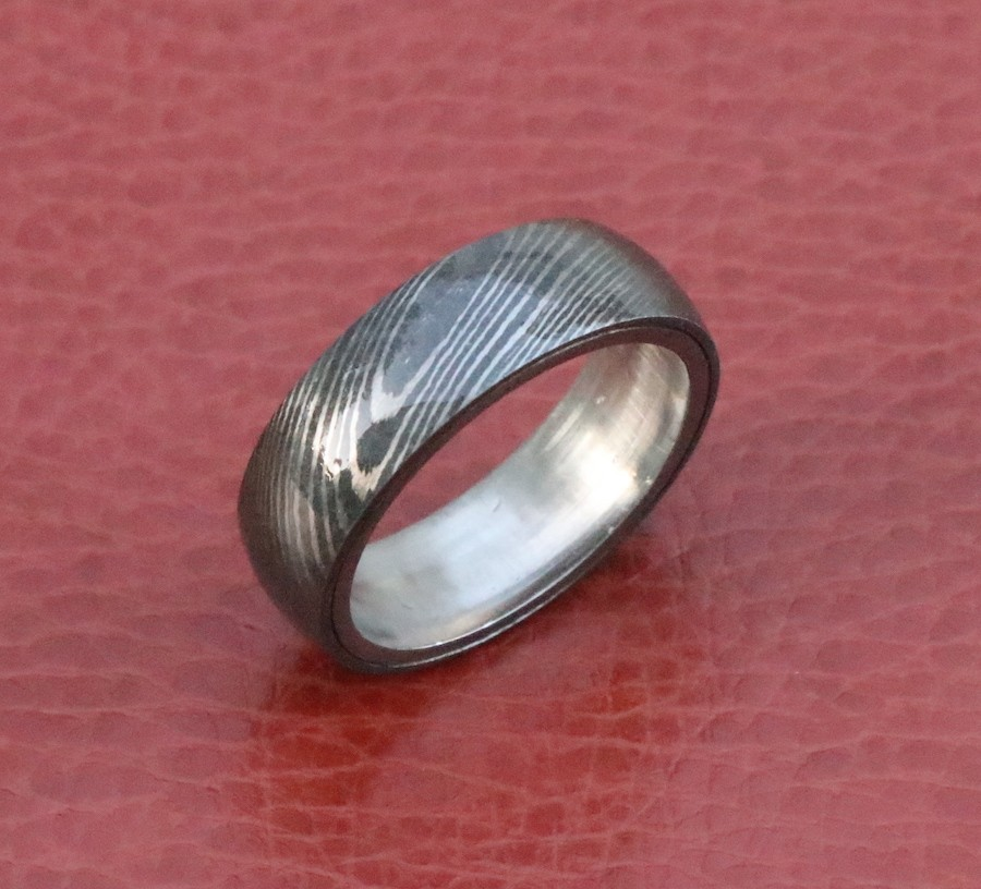 Damascus steel wedding ring with stainless steel inlay